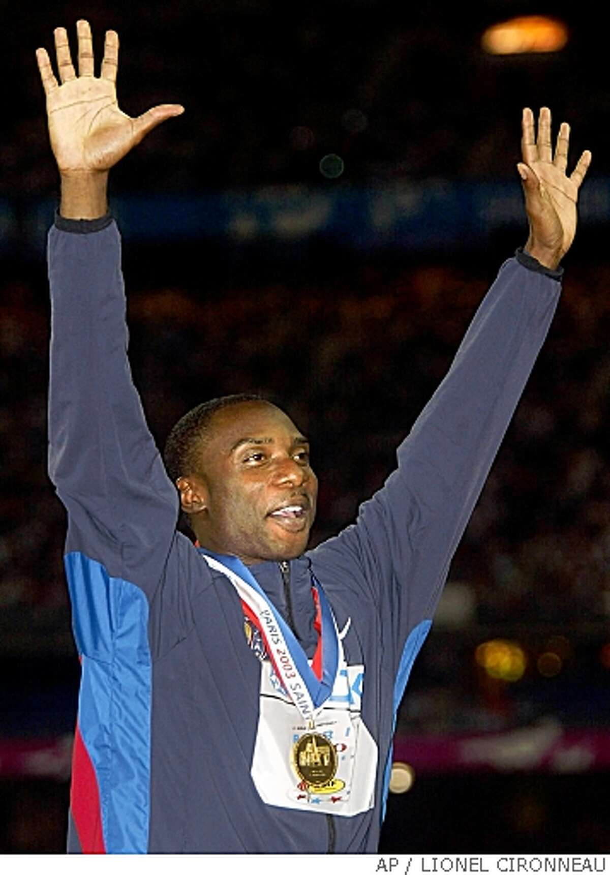 Jerome Young of the USA celebrates the gold medal he won in the men's 400-meter at the World Athletics Championships, at the Stade de France in Saint Denis, north of Paris, Wednesday, Aug. 27, 2003. Sprinter Young, a central figure in a doping case that could cost the U.S. relay team its gold medal from Sydney, was banned for life by the U.S. Anti-Doping Agency on Wednesday, Nov. 10, 2004, following his second positive test for a banned drug. (AP Photo/Lionel Cironneau,file)