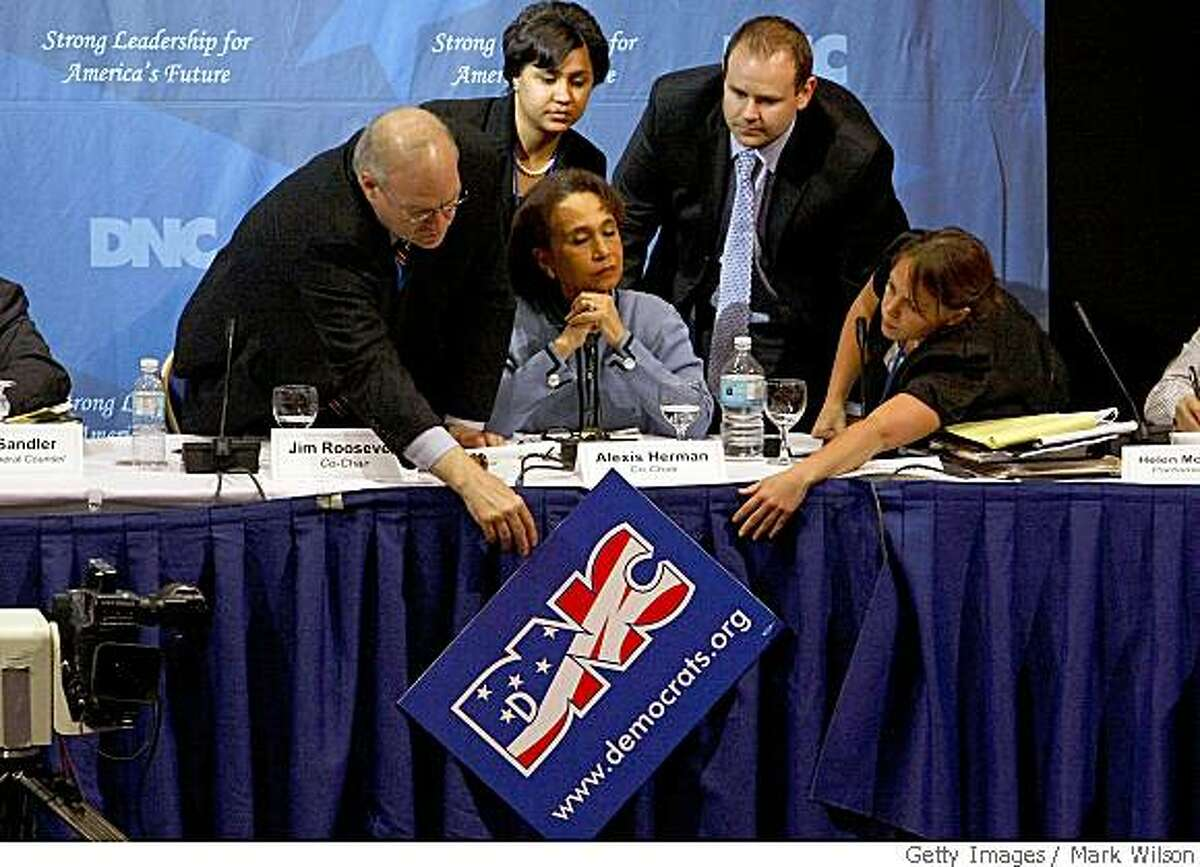 WASHINGTON - MAY 31: Democratic National Committee (DNC) Co-Chair Alexis Herman (C) watches as DNC Co-Chair Jim Roosevelt (L), and others try to fix a DNC poster that came loose during a DNC meeting at the Marriott Park Wardman hotel May 31, 2008 in Washington DC. The Democratic National Committee's Rules and Bylaws Committee is meeting today at the hotel to decide what to do with delegates from Florida and Michigan. (Photo by Mark Wilson/Getty Images)