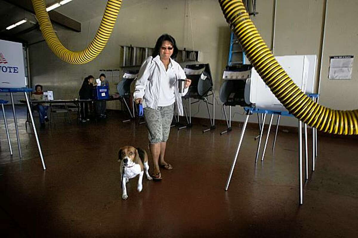 At Fire Station 64 in South San Francisco, Calif., Amy Matthews with her dog, Cosmo, walk in a vote by mail ballot on Tuesday, November 3, 2009. People are voting on a 1 percent hotel tax to help maintain police and fire stations.
