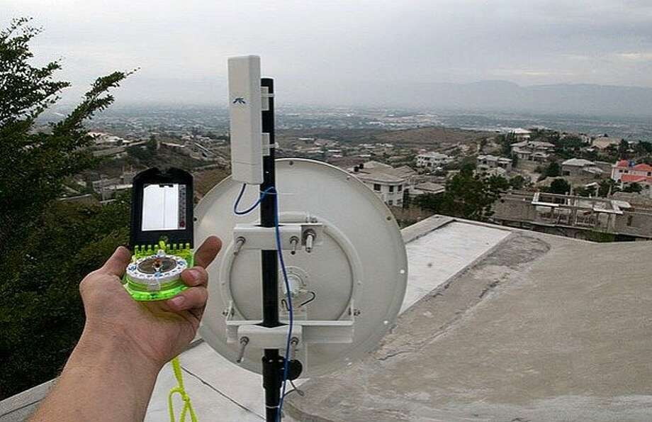 Andris Bjornson of the Inveneo team aligns antennas for a WiFi network across Port-au-Prince right after the earthquake. Photo: Courtesy Of Inveneo