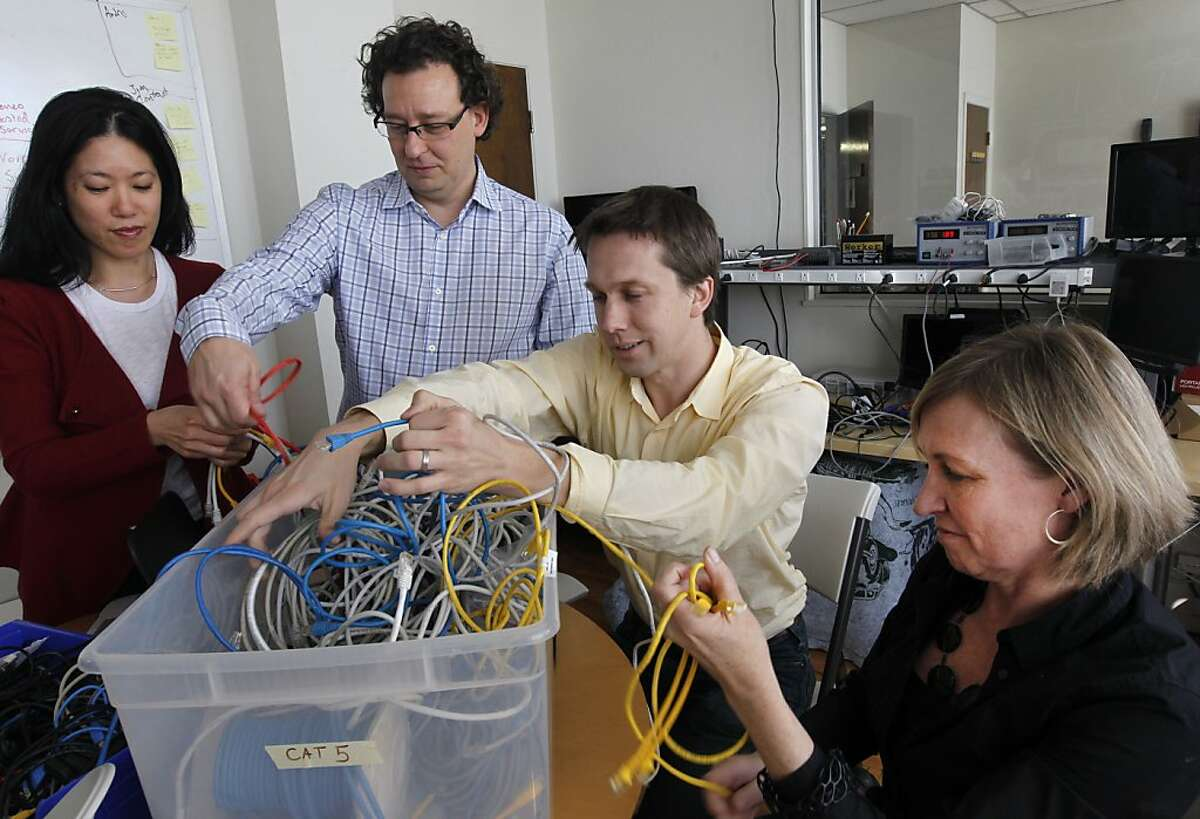 Inveneo company officers Lisa Lin, Mark Summer, Andris Bjornson and Kristin Peterson untangle ethernet cables at the company's South of Market office in San Francisco, Calif. on Friday, Jan. 27, 2012. Inveneo's mission is to set up wireless broadband coverage in developing nations in eastern Africa, Haiti and many others.