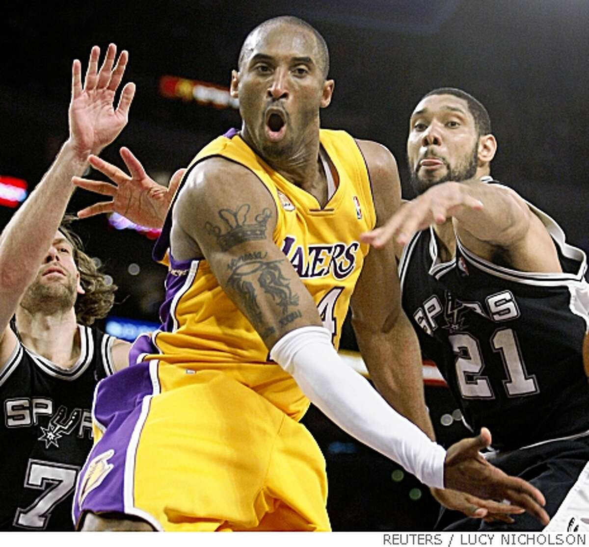 Los Angeles Lakers' Kobe Bryant passes off after driving between San Antonio Spurs' Tim Duncan (R) and Fabricio Oberto (L) during Game 2 of their NBA Western Conference final basketball playoff series in Los Angeles, May 23, 2008. REUTERS/Lucy Nicholson (UNITED STATES)