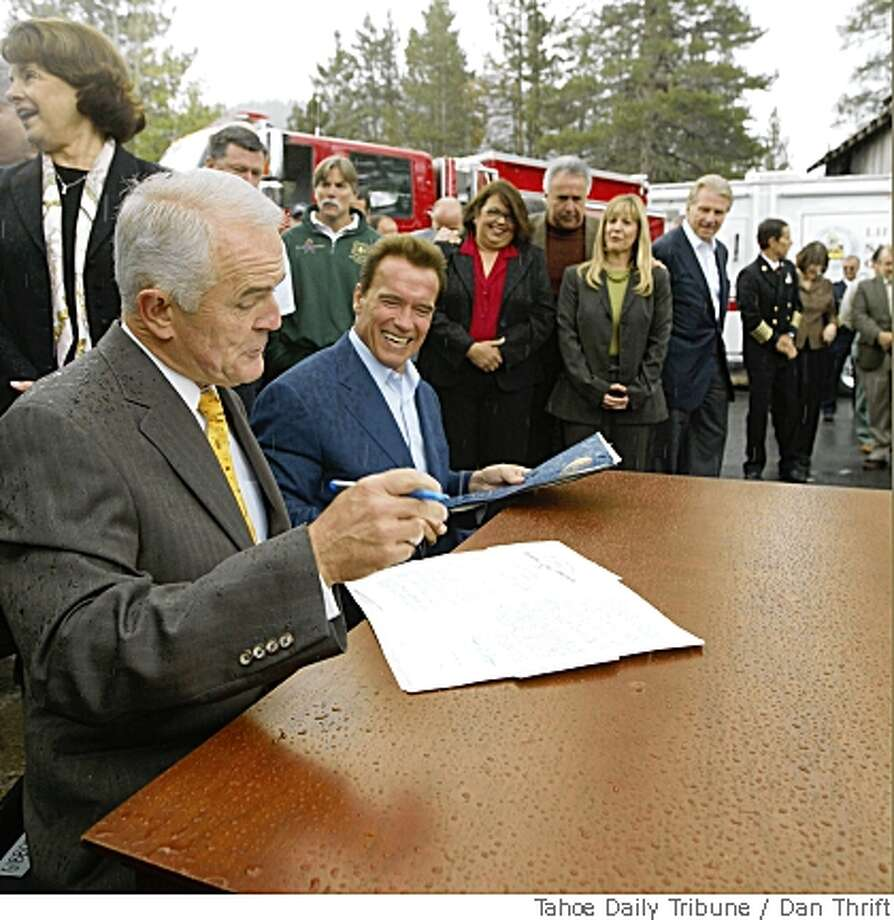 Nevada Gov. Jim Gibbons, left, and California Gov. Arnold Schwarzenegger quickly sign the recommendation of the California-Nevada Tahoe Basin Fire Commission report on Tuesday May 27, 2008 as a cloud burst opens on the ceremony at Lake Valley Fire Protection District Station #7 in Meyers, Calif. (AP Photo/Tahoe Daily Tribune,Dan Thrift) Photo: Dan Thrift, Tahoe Daily Tribune