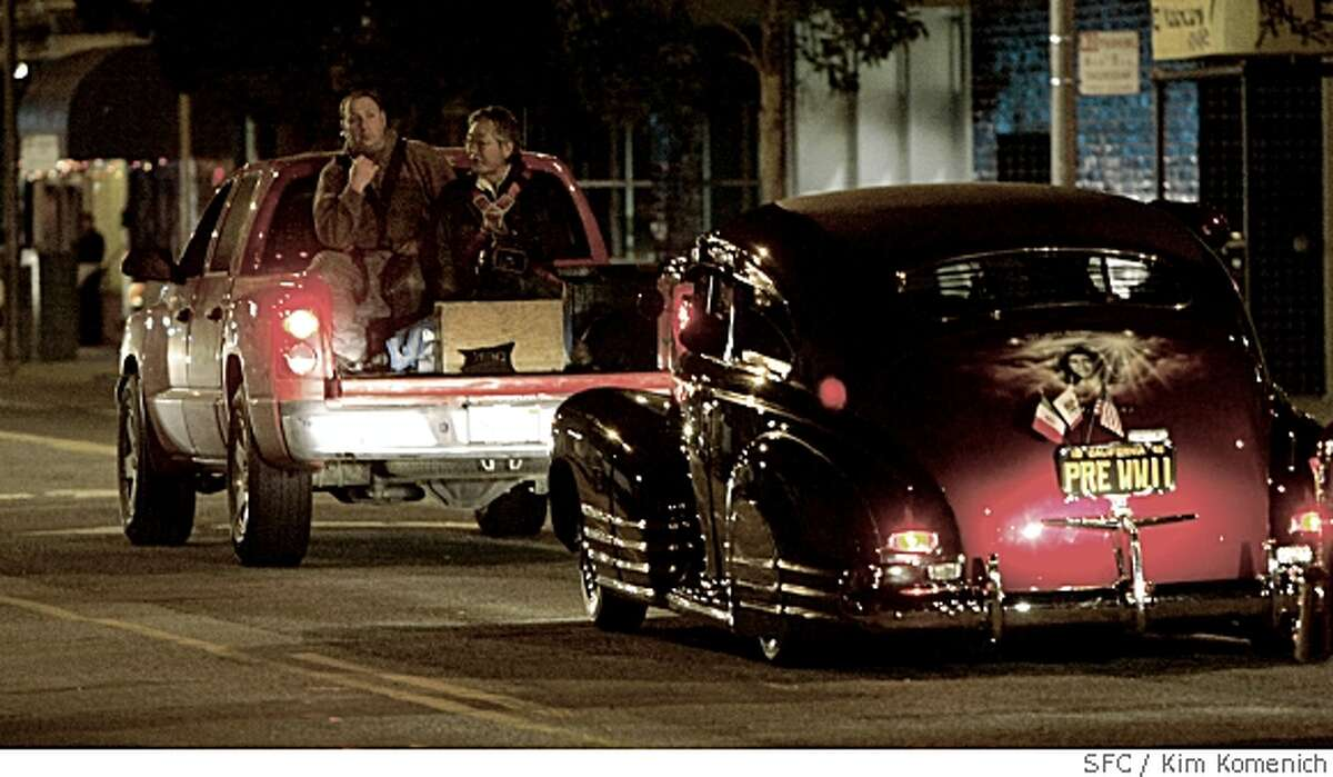 Cameramen in a truck film low rider cars during the filming of