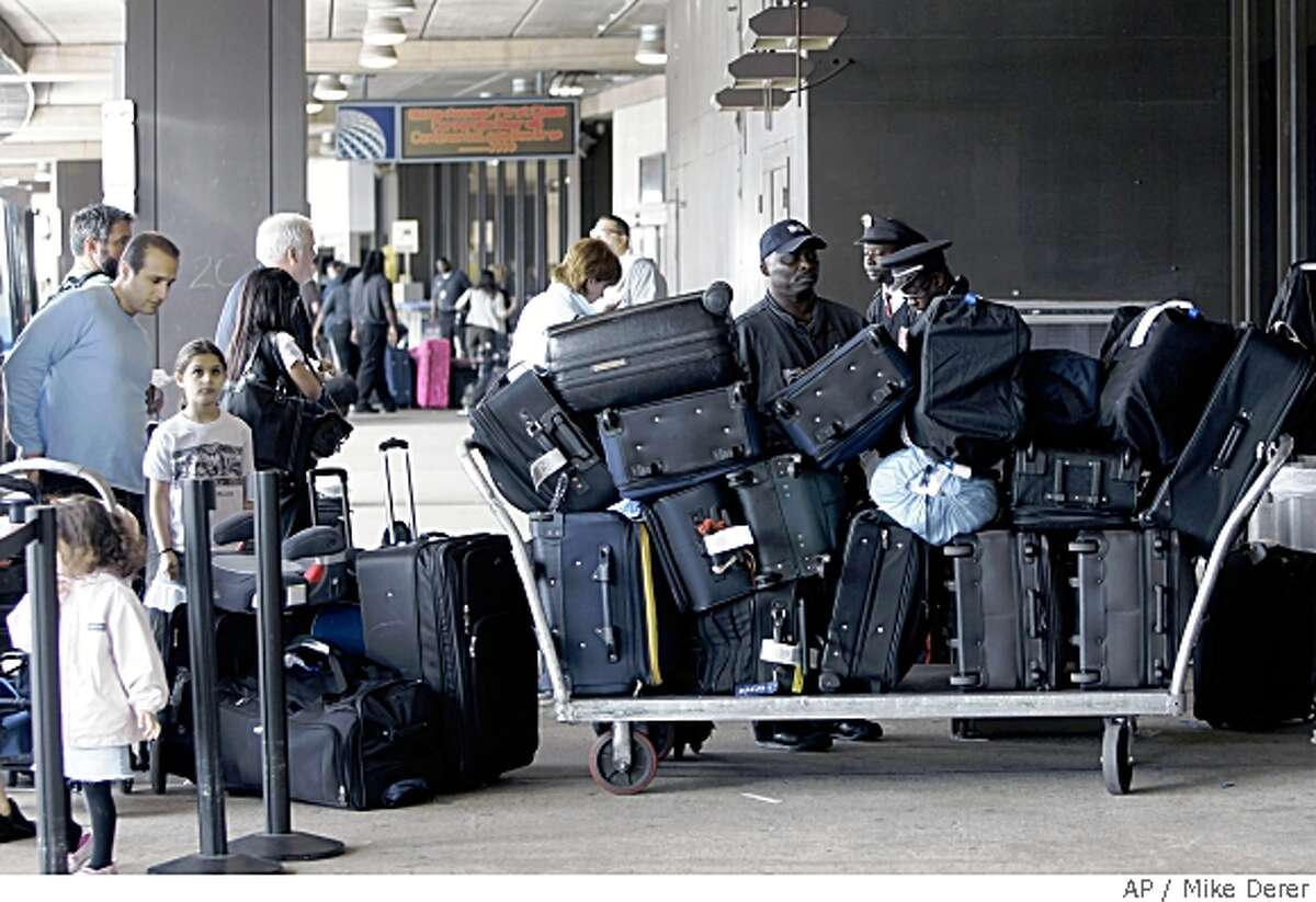 Bags are checked in at curbside at Newark International Airport in Newark, N.J., Thursday, May 22, 2008. Higher fares and new fees are irritating air travelers, but airlines still can't raise money or cut flights fast enough to cover ever-higher fuel prices. (AP Photo/Mike Derer)