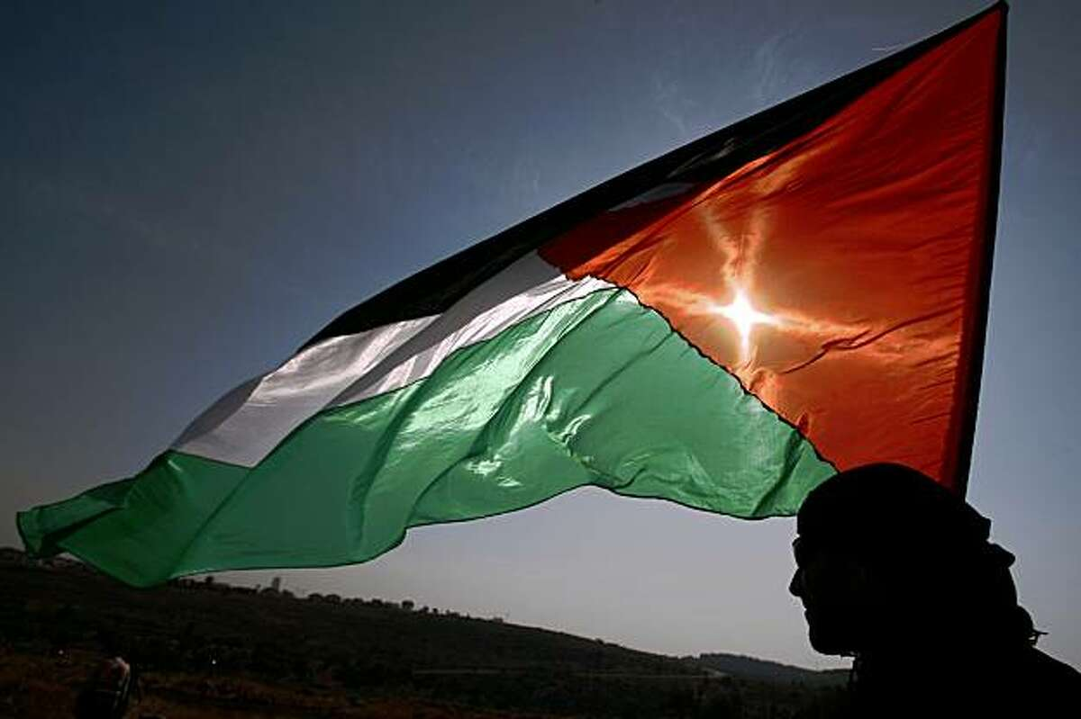 A Palestinian protestor holds his national flag during a demonstration against Israel's controversial separation barrier in the West Bank village of Nilin, near Ramallah on October 23, 2009. US Secretary of State Hillary Clinton offered President Barack Obama a downbeat report on his administration's so-far frustrated efforts to forge Middle East peace. TOPSHOTS/AFP PHOTO/ABBAS MOMANI (Photo credit should read ABBAS MOMANI/AFP/Getty Images)