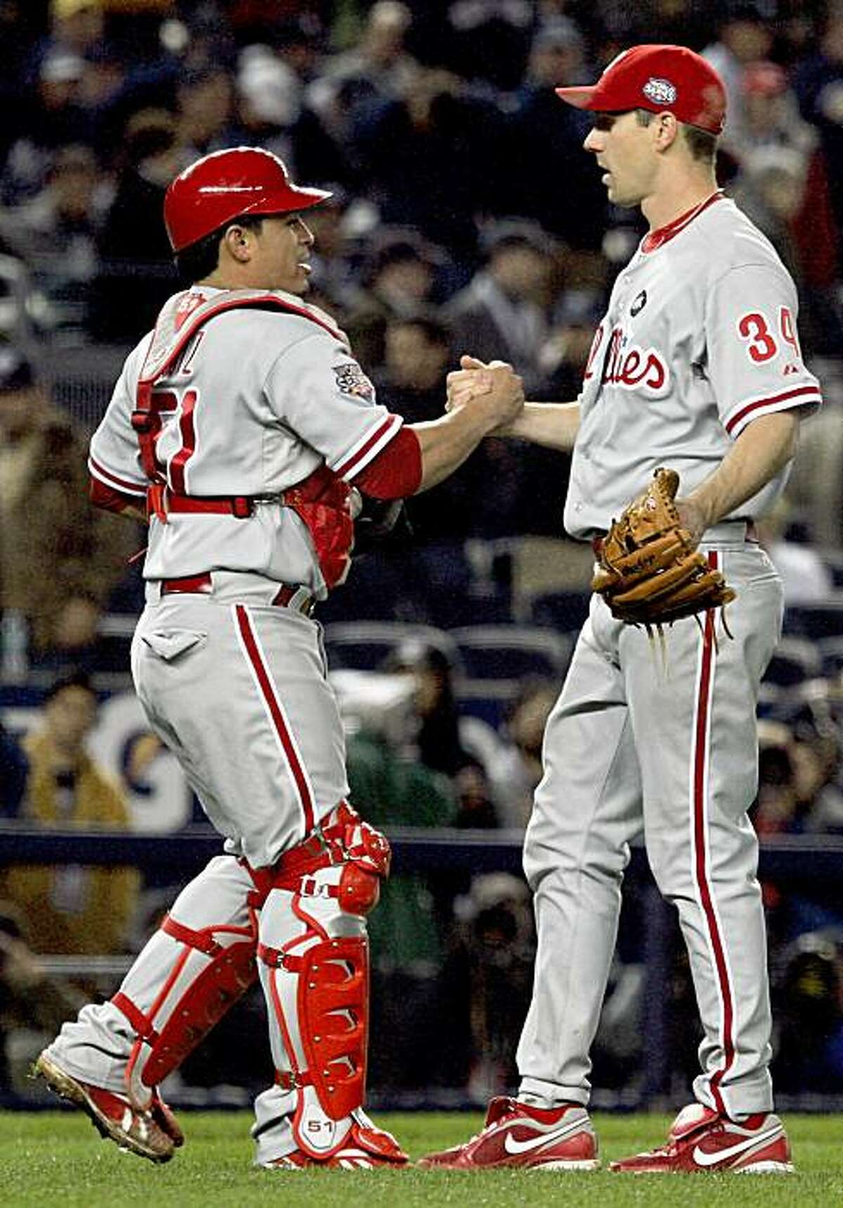 NEW YORK - OCTOBER 28: (L-R) Carlos Ruiz #51 and Cliff Lee #34 of the Philadelphia Phillies celebrate after their 6-1 win against the New York Yankees in Game One of the 2009 MLB World Series at Yankee Stadium on October 28, 2009 in the Bronx borough of New York City. (Photo by Jim McIsaac/Getty Images)