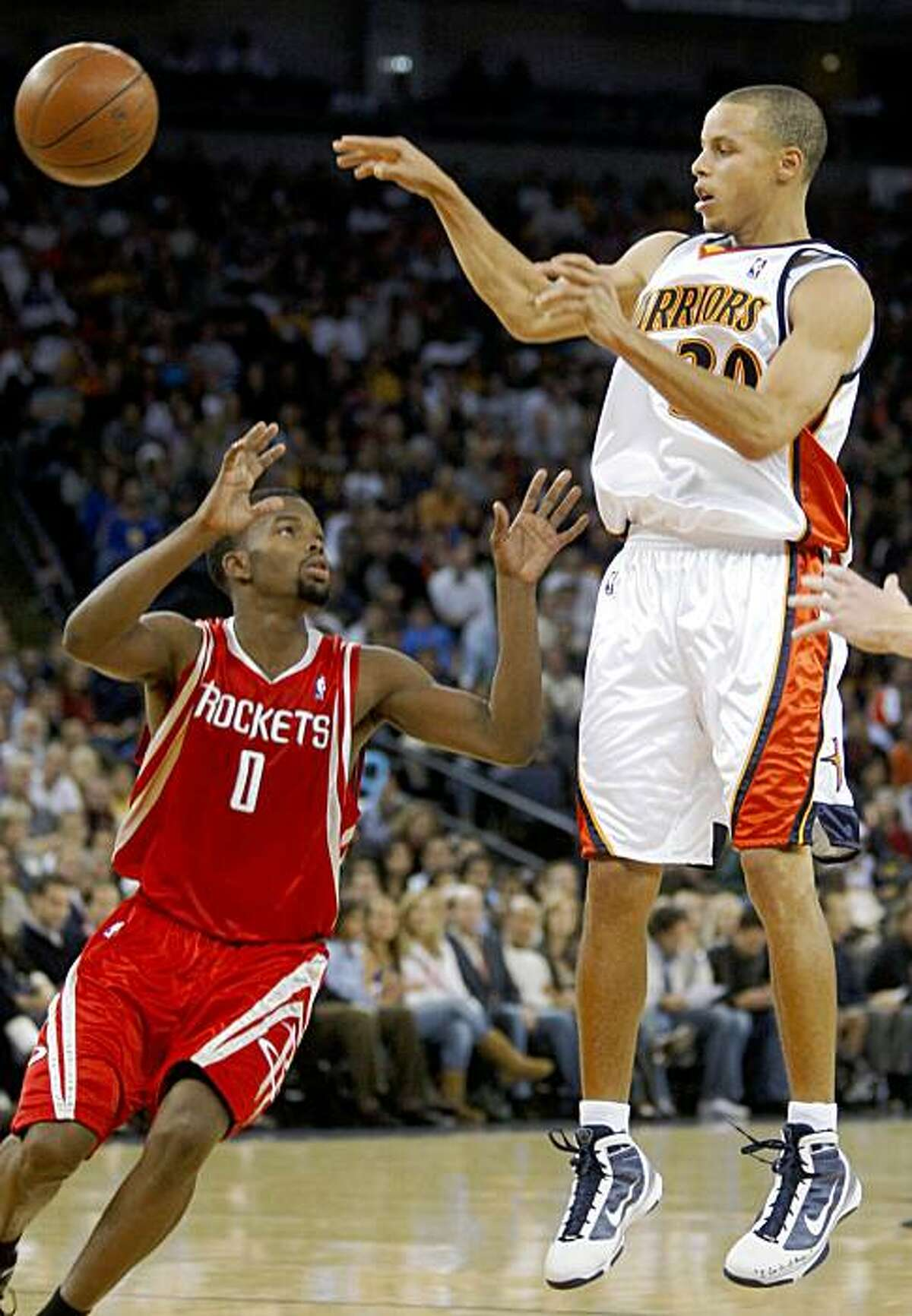 Golden State Warriors' Stephen Curry, right, passes away from Houston Rockets' Aaron Brooks during the second half of an NBA basketball game Wednesday, Oct. 28, 2009, in Oakland, Calif. (AP Photo/Ben Margot)