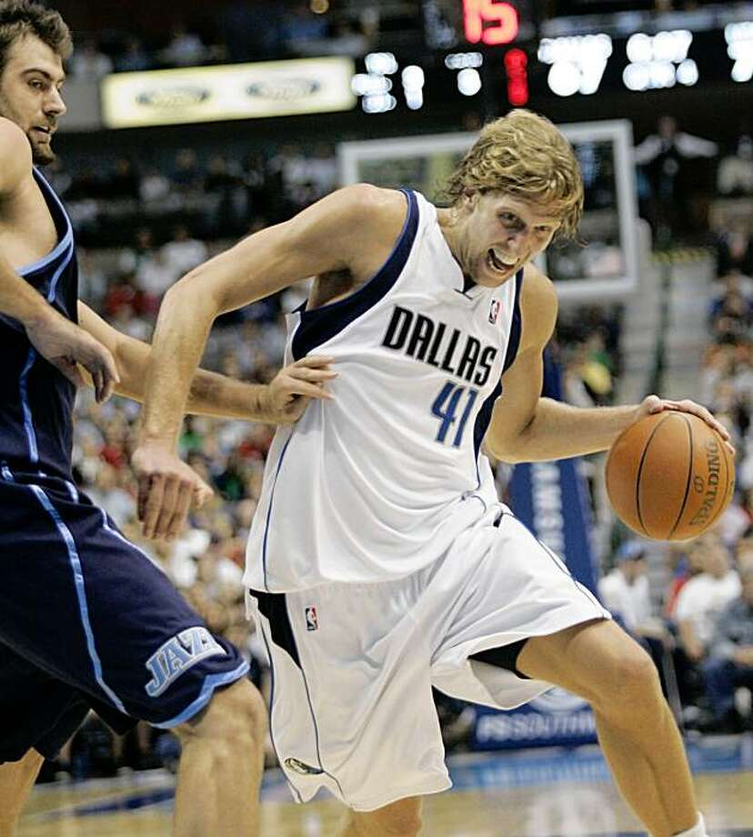 Utah Jazz center Mehmet Okur, left, from Turkey defends against Dallas Mavericks forward Dirk Nowitzki (41) from Germany as he drives to the basket in the second half of an NBA basketball game in Dallas, Tuesday, Nov. 3, 2009. The Mavericks won 96-85.  (AP Photo/Donna McWilliam) Photo: Donna McWilliam, AP