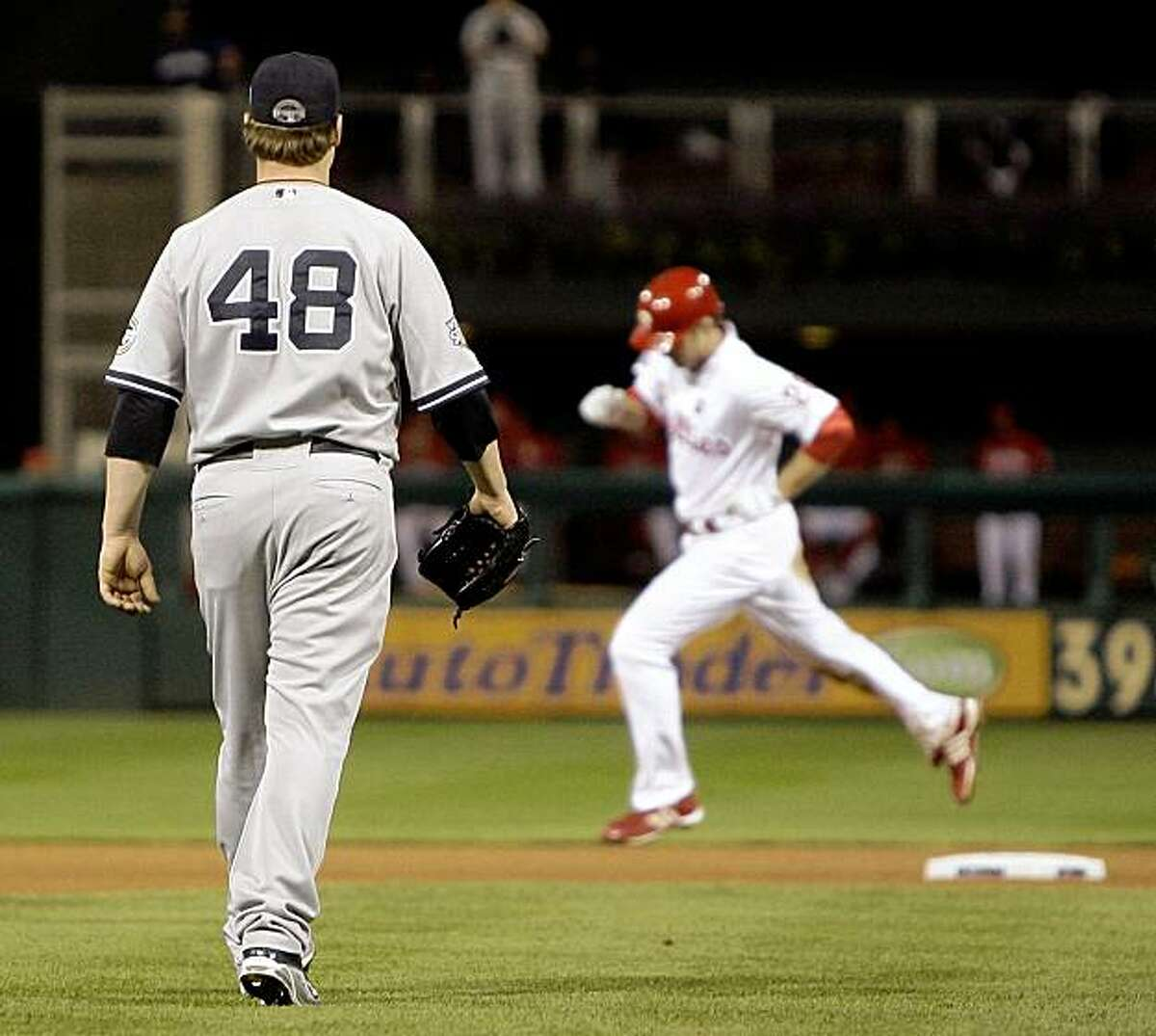 New York Yankees' Phil Coke watches as Philadelphia Phillies' Chase Utley rounds the bases after Utley hit a home run during the seventh inning of Game 5 of the Major League Baseball World Series Monday, Nov. 2, 2009, in Philadelphia. (AP Photo/Matt Slocum)