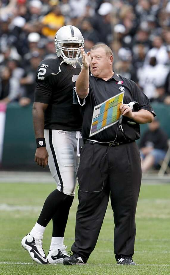 During a third-quarter timeout Sunday at the Oakland Coliseum, Raiders coach Tom Cable and quarterback JeMarcus Russell go over a play. Photo: Brant Ward, The Chronicle