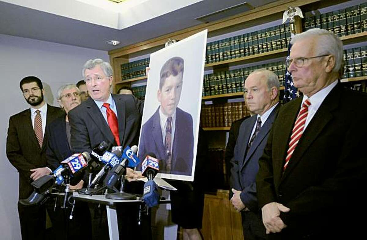 Attorney Thomas S. Neuberger, center, holds up a 1966 photograph of alleged sex abuse victim John Vai, second from right, now 57, of Wilmington, Del. during a news conference Monday, Oct. 19, 2009 at The Neuberger Firm's law offices in Wilmington, Del. Attorney Stephen J. Neuberger, left, alleged abuse victim Mike Jordan, second from left, 64, of Wilmington, and alleged abuse victim Mike Snowden, right, 61, of Wilmington, also attended the news conference. Delware's Catholic Diocese of Wilmington filed for federal bankruptcy protection late Sunday, delaying Vai's sex abuse lawsuit that had been set to start Monday in Kent County Superior Court, the first of eight Catholic Church abuse trials scheduled in Delaware. (AP Photo/ Steve Ruark)