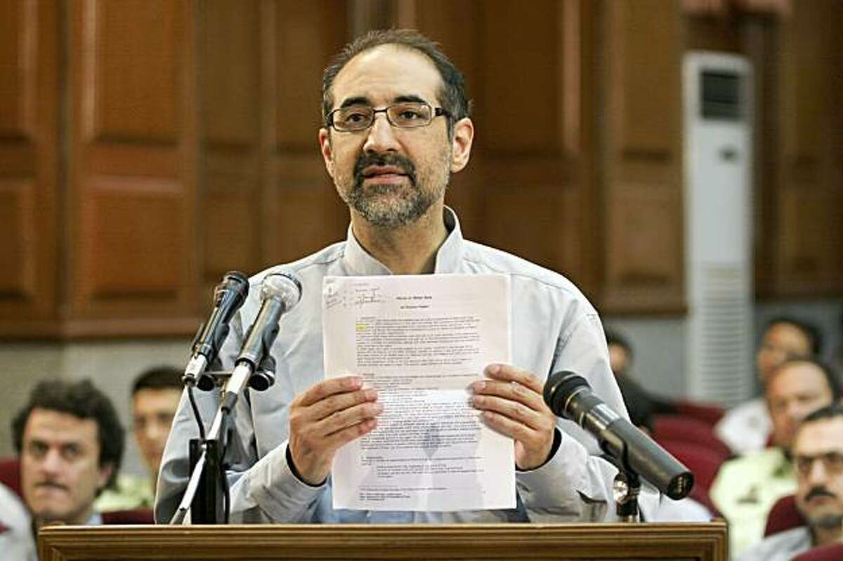 In this Tuesday, Aug. 25, 2009 photo released by the Iranian Labor News Agency (ILNA), Iranian-American scholar Kian Tajbakhsh hold a piece of paper as he defends himself during the trial of dozens of opposition activists and protesters in Tehran's Revolutionary Court, Iran. A special court formed after Iran's post-election unrest has convicted Tajbakhsh and sentenced him to more than 12 years in prison, state media said Tuesday, Oct. 20, 2009. (AP Photo/ILNA,Houshang Hadi) EDITORS NOTE AS A RESULT OF AN OFFICIAL IRANIAN GOVERNMENT BAN ON FOREIGN MEDIA COVERING SOME EVENTS IN IRAN, THE AP WAS PREVENTED FROM INDEPENDENT ACCESS TO THIS EVENT