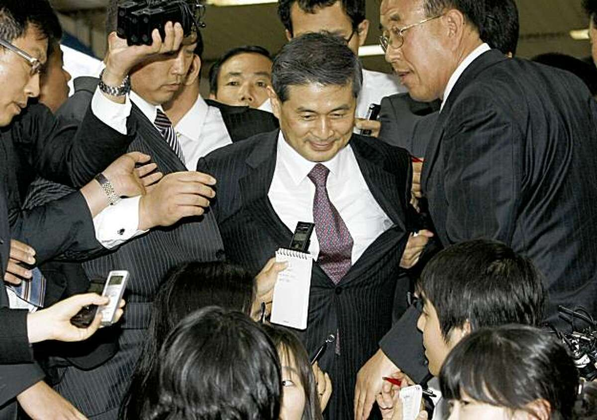 South Korean disgraced scientist Hwang Woo-suk, center, leaves after his trial at the Seoul Central District Court in Seoul, South Korea, Monday, Oct. 26, 2009. Hwang, who falsely claimed to have achieved major breakthroughs in stem cell research, was convicted Monday of charges connected to his research, but avoided jail as the court suspended a two-year prison term for him. (AP Photo/Ahn Young-joon)