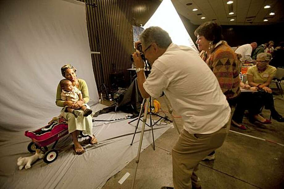 Joe Ramos (L) a volunteer for story project (an arm of project homeless connect) takes a photo of Andrea Edwards and her one year old grandson Charlie Bonner at Project Homeless Connect at the Bill Graham Civic Auditorium October 28, 2009 in San Francisco, Calif. (Photograph by David Paul Morris/Special to the Chronicle). Photo: David Paul Morris, Special To The Chronicle