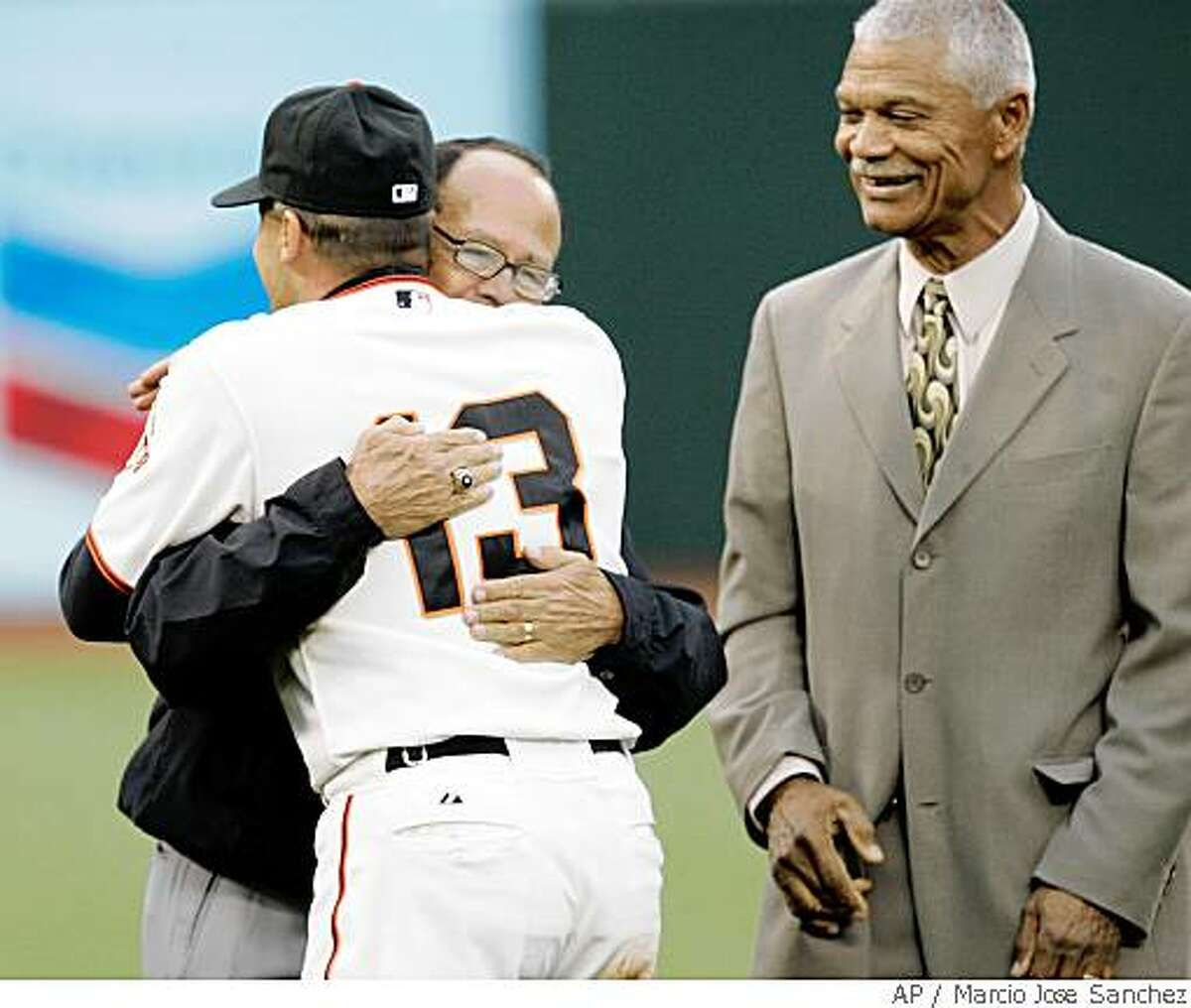 San Francisco Giants shortstop Omar Vizquel (13) is hugged by former shortstop Luis Aparicio as former Giants manager Felipe Alou, right, looks on as Vizquel is honored for becoming the all-time leader in games played at shortstop before the start of a baseball game against the San Diego Padres in San Francisco, Friday, May 30, 2008. Associated Press photo by Marcio Jose Sanchez