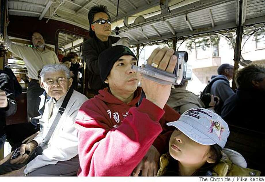 Ron Zamora from Paranaque, Philippines captures  video moments over her daughter, Angelika Zamora's head, 9, while riding down the Hyde Street cable car on Thursday May, 29, in San Francisco, Calif. The San Francisco Convention & Visitors Bureau, Thursday released 2007 tourism figures, which suggested tourism would be up partly due the week U.S. dollar. Photo: Mike Kepka, The Chronicle