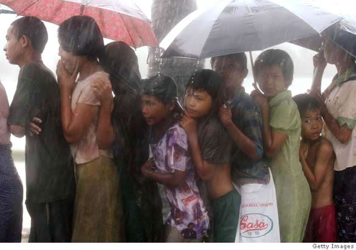 ###Live Caption:DEDAYA, MYANMAR - MAY 13: Burmese people queue up for food in the rain as aid begins to arrive following last week's Cyclone on May 13, 2008, in Dedaya, Myanmar. It has been estimated that more than 100,000 people were killed by Cyclone Nargis. International Aid Agencies are continuing efforts to deliver aid into Myanmar in order to assist up to one million people made homeless. (Photo by Getty Images)###Caption History:DEDAYA, MYANMAR - MAY 13: Burmese people queue up for food in the rain as aid begins to arrive following last week's Cyclone on May 13, 2008, in Dedaya, Myanmar. It has been estimated that more than 100,000 people were killed by Cyclone Nargis. International Aid Agencies are continuing efforts to deliver aid into Myanmar in order to assist up to one million people made homeless. (Photo by Getty Images)###Notes:Cyclone Aid Starts To Trickle Into Burma###Special Instructions: