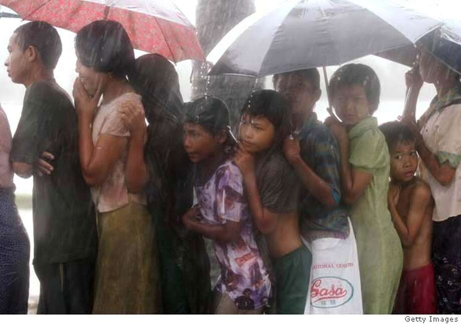 ###Live Caption:DEDAYA, MYANMAR - MAY 13: Burmese people queue up for food in the rain as aid begins to arrive following last week's Cyclone on May 13, 2008, in Dedaya, Myanmar. It has been estimated that more than 100,000 people were killed by Cyclone Nargis. International Aid Agencies are continuing efforts to deliver aid into Myanmar in order to assist up to one million people made homeless. (Photo by Getty Images)###Caption History:DEDAYA, MYANMAR - MAY 13: Burmese people queue up for food in the rain as aid begins to arrive following last week's Cyclone on May 13, 2008, in Dedaya, Myanmar. It has been estimated that more than 100,000 people were killed by Cyclone Nargis. International Aid Agencies are continuing efforts to deliver aid into Myanmar in order to assist up to one million people made homeless. (Photo by Getty Images)###Notes:Cyclone Aid Starts To Trickle Into Burma###Special Instructions: Photo: Getty Images
