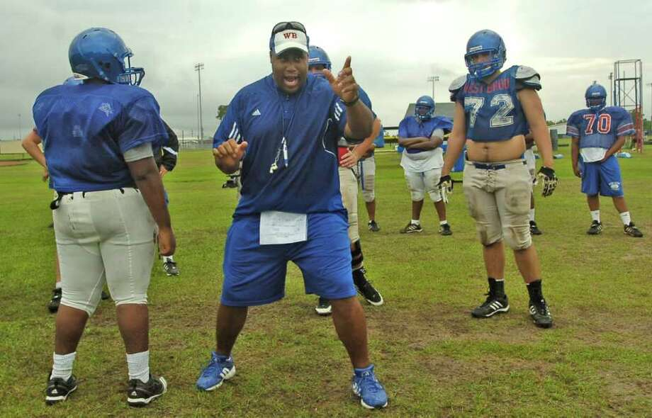 Offensive linemen go through a drill as their Offense Line Coach Joe Bowser, center, overseas how they do it, yells at them if they don't do it just the way he wants it done, and then shows them how he wants it done.  West Brook High School started spring football practice Monday afternoon.  Dave Ryan/The Enterprise Photo: Dave Ryan