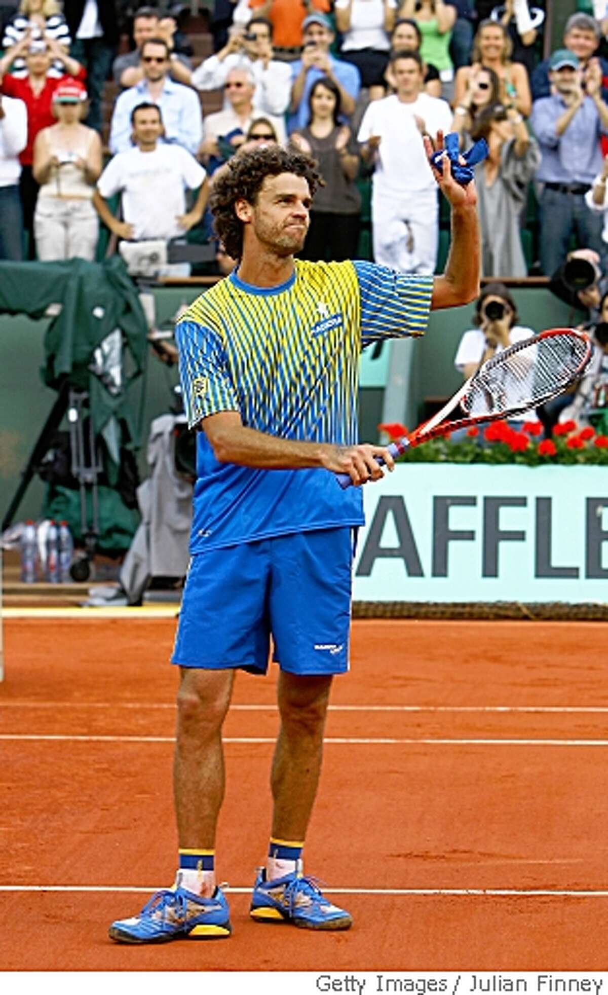 PARIS - MAY 25: Gustavo Kuerten of Brazil applauds the fans after his career ending defeat during Men's Singles first round match against Paul-Henri Mathieu of France on day one of the French Open at Roland Garros on May 25, 2008 in Paris, France. The French Open with be Kuertens last tournament before retiring (Photo by Julian Finney/Getty Images)