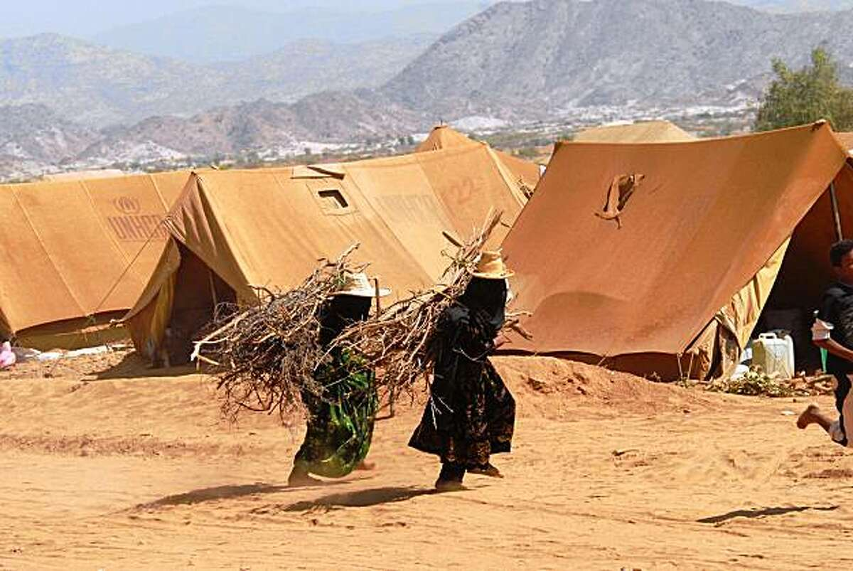 Yemeni women carry fire wood on their backs as they walk past tents in the Marzaq camp set-up for internally displaced Yemenis in the northwestern province of Hajjah, near the Saudi Arabian border, on October 19, 2009. The UN says some 150,000 people have been displaced in northern Yemen in the past five years, including 55,000 since August 11 when armed hostilities resumed between Shiite rebels and the military. AFP PHOTO/KHALED FAZAA (Photo credit should read KHALED FAZAA/AFP/Getty Images)