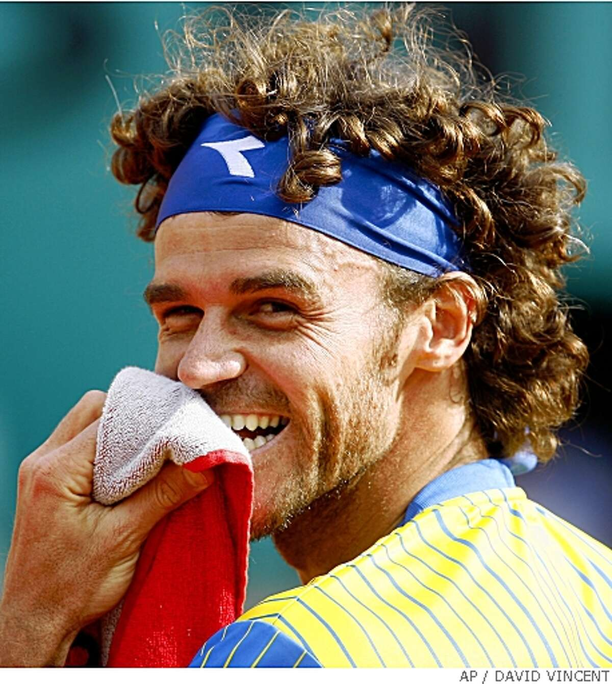 Three time French Open winner Gustavo Kuerten, of Brazil, smiles as he plays France's Paul-Henri Mathieu during their first round match of the French Open tennis tournament, Sunday May 25, 2008 at the Roland Garros stadium in Paris. Kuerten bids farewell to tennis at the site of his biggest triumphs. Mathieu won 6-3, 6-4, 6-2 . (AP Photo/David Vincent)
