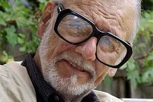 """George Romero, the filmmaker most known for his """"Night of the Living Dead,"""" and its' subsequent sequels, talks about a new project tentatively called """"Land of the Dead"""" while sitting in the back yard of his home in Pittsburgh's Shadyside neighborhood on Friday July 23, 2004. (AP Photo/Keith Srakocic) Ran on: 06-26-2005  Ran on: 03-31-2006  George A. Romero, the zombie movie guy, never neglected social satire in his oeuvre."""