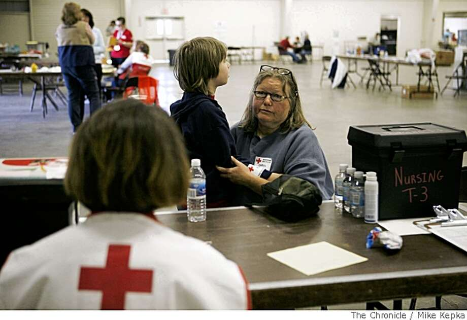 After being force to leave her home yesterday because of wildfires that spread through the Santa Cruz Mountains, Cheryl Hamel with her son Eli Hamel, 9, tries to figure out what their next move should be as the seek help at the Red Cross shelter set up at the Santa Cruz County Fairdgrounds on Friday, May 23, in Watsonville, Calif. Photo by Mike Kepka / San Francisco Chronicle Photo: Mike Kepka, SFC