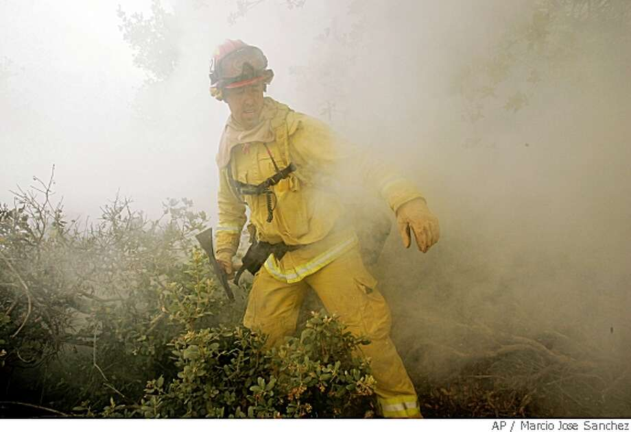 Capt. Jason Falarski, of the Santa County Fire Dept., walks through the smoke created by the Summit fire in the Santa Cruz Mountains west of Gilroy, Calif., Friday, May 23, 2008. Calmer winds and heavy fog brought some much-needed relief Friday morning to firefighters working to rein in a wildfire that quickly consumed a dozen buildings in the Santa Cruz Mountains a day earlier.  (AP Photo/Marcio Jose Sanchez) Photo: Marcio Jose Sanchez, AP