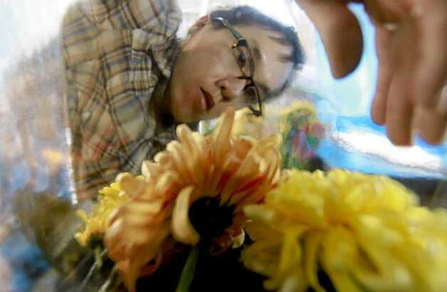 "Artist Phillip Hua, seen through a glass vase, works on his art piece at 984 Market St., as part of the ""Art in Storefronts"" project, sponsored by the San Francisco Arts Commission in San Francisco, Calif. on Friday October 23, 2009. Photo: Michael Macor, The Chronicle"