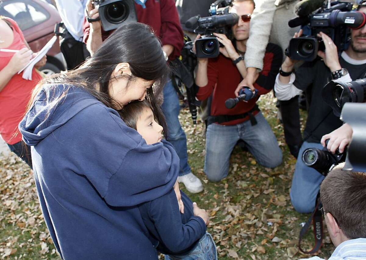 Six-year-old Falcon Heene, front right, is hugged by his mother, Mayumi, as television photographers crowd around them after a news conference outside the family's home in Fort Collins, Colo., after Falcon Heene was found hiding in a box in a space above the garage on Thursday, Oct. 15, 2009. Falcon Heene at first had been reported to be aboard a flying-saucer-shaped balloon fashioned by his father and then carried by high winds on to the plains of eastern Colorado.