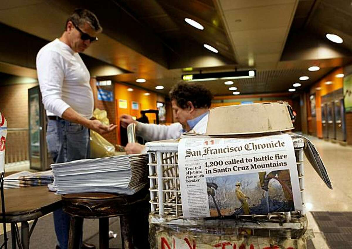 Newspaper vendor Rick Gaub (right) helps a customer with change at his stand in an underground rail station Monday in San Francisco.
