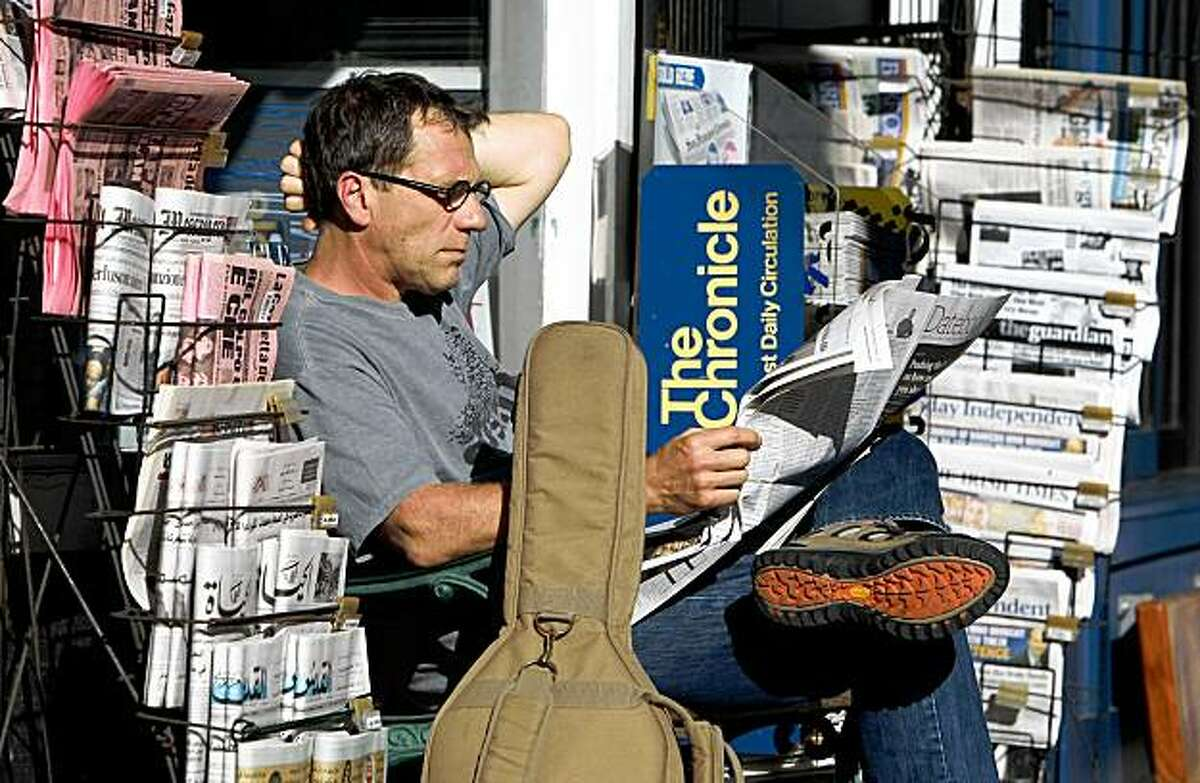 Brian Keeney reads the San Francisco Chronicle as he sits on a bench in front of a newsstand Monday in San Francisco.