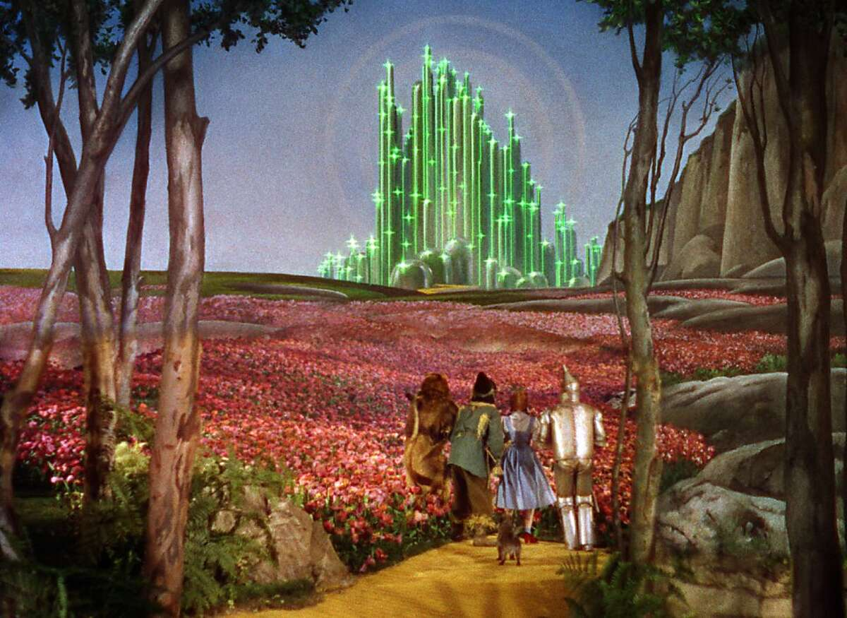 Dorothy, the Scarecrow, the Lion, and the Tin Man make their way to the Emerald City in