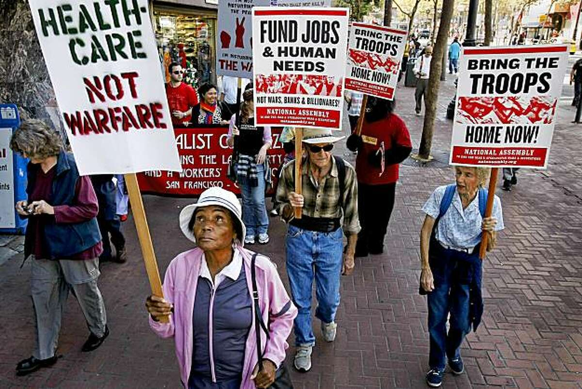 Jessie McElroy, (front left) of Oakland joins other protesters as they make their way down Market Street on the sidewalks during an anti-war march against the war in Afghanistan.