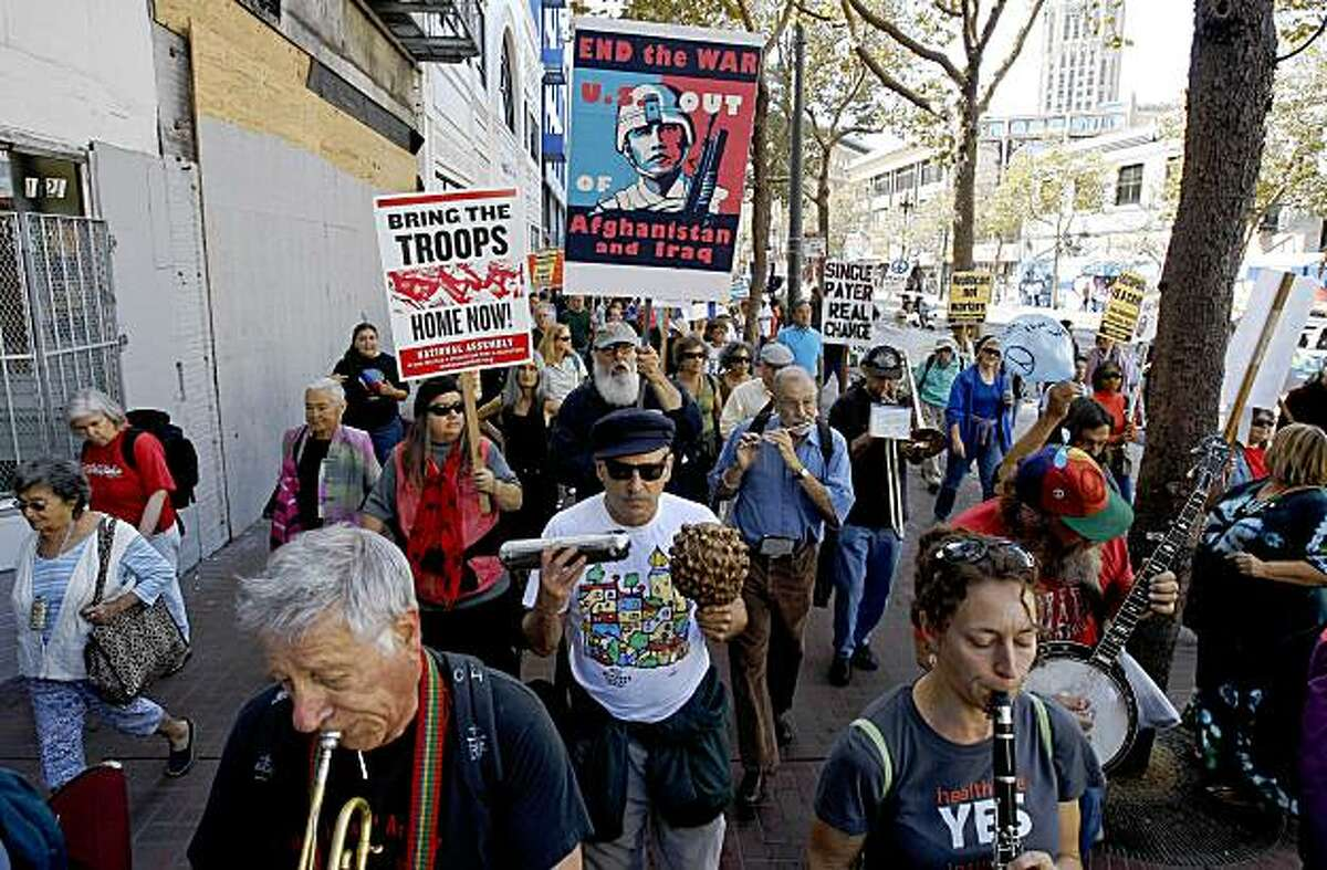 Protesters make their way down Market street on the sidewalks during an antiwar march.
