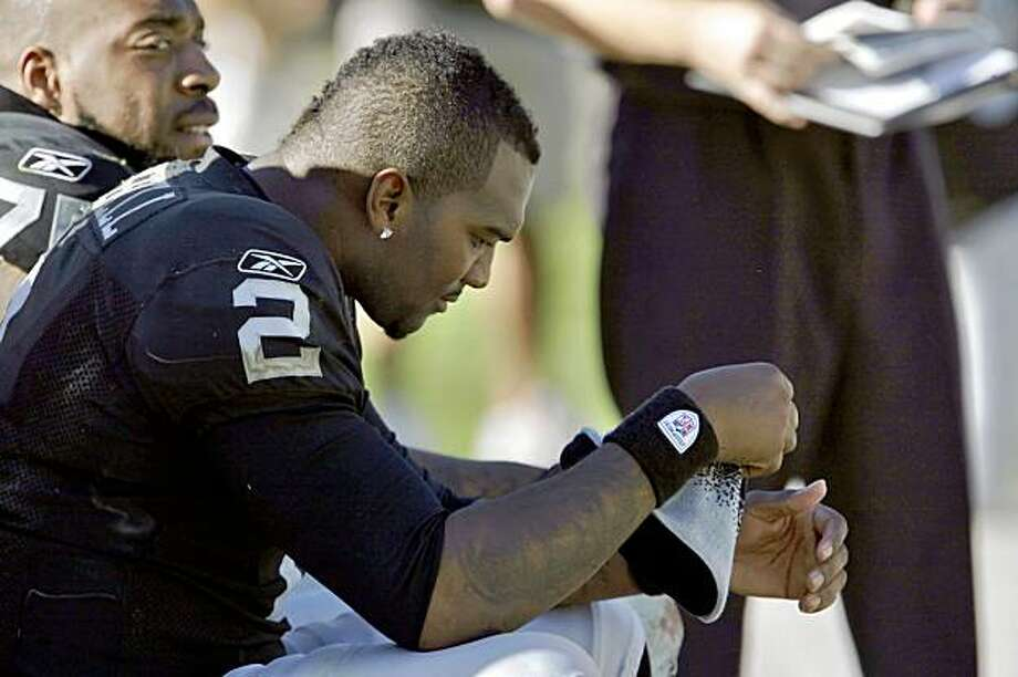 JaMarcus Russell sits on the bench after being taken out of the game in the second quarter. Photo: Carlos Avila Gonzalez, The Chronicle