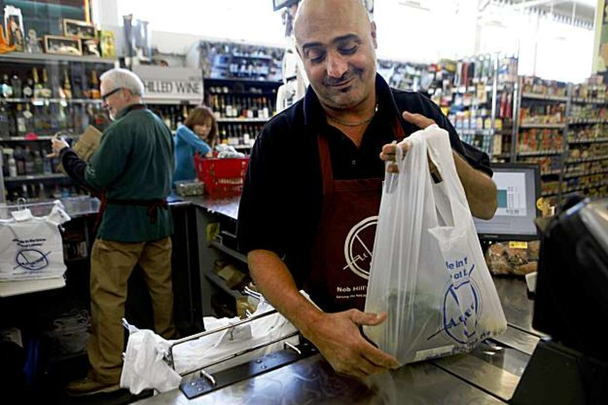 Twenty years after the Loma Prieta earthquake hit San Francisco, Joseph Omran, owner of the Le Beau market on Nob Hill, tends to his duties at the cash register. During the days following the quake he set up large barbecues on the sidewalks to help ease trauma for the surrounding neighborhood.