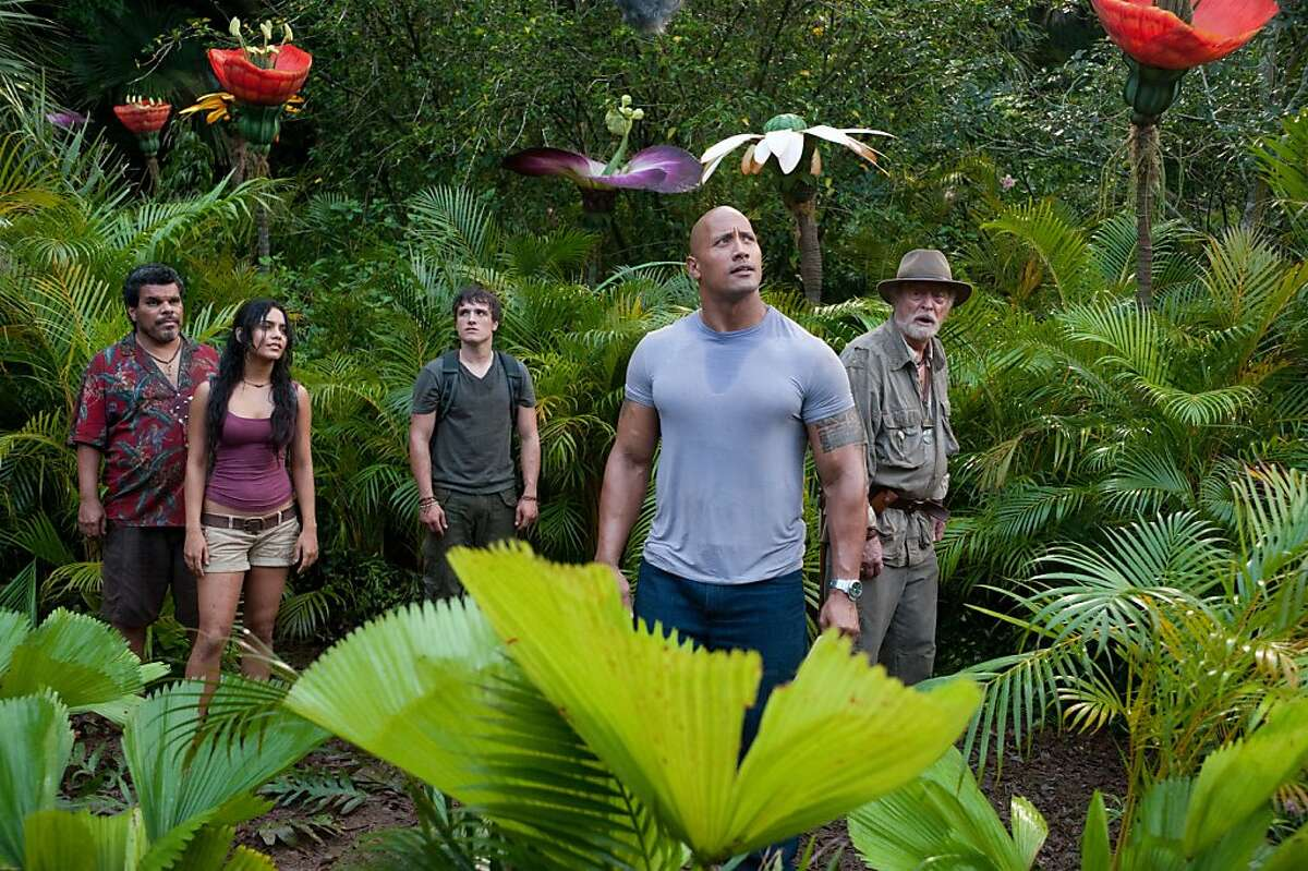 In this image released by Warner Bros. Pictures, from left, Luis Guzman, Vanessa Hudgens, Josh Hutcherson, Dwayne Johnson and Michael Caine are shown in a scene from