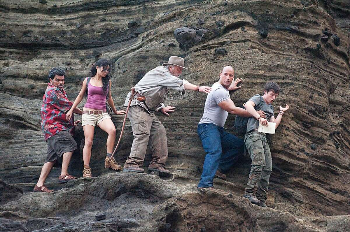 In this image released by Warner Bros. Pictures, from left, Luis Guzman, Vanessa Hudgens, Michael Caine, Dwayne Johnson and Josh Hutcherson are shown in a scene from