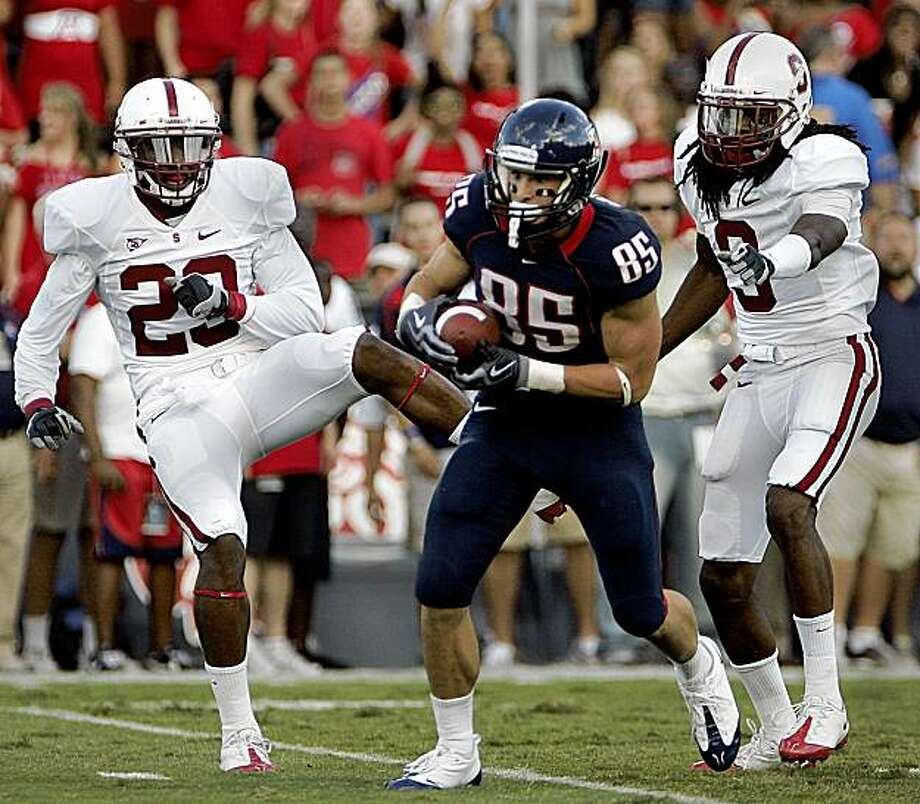 Arizona's David Douglas (85) makes a catch and runs to the endzone between Stanford's Mark Watley (23) and Joe Perkins (9) in the first half of an NCAA college football game at Arizona Stadium in Tucson, Ariz., Saturday, Oct. 17, 2009.   (AP Photo/Wily Low) Photo: Wily Low, AP