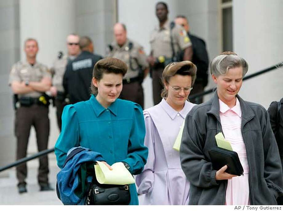 Members of the Fundamentalist Church of Jesus Christ of Latter Day Saints, front, walk out of the Tom Green County Courthouse as Sheriffs deputies, rear, look on during the first day of child custody hearings in San Angelo, Texas, Thursday, April 17, 2008. (AP Photo/Tony Gutierrez) Photo: Tony Gutierrez
