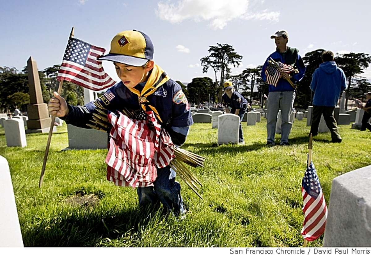 SAN FRANCISCO, CA - MAY 27: Ethan Frankes 7, from Mill Valley Pack 1 puts flags in front of gravesites at the San Francisco National Cemetary in the Presidio on May 27, 2006 in San Francisco, California. Over 600 scouts from the bay area put down 31,414 flags at the cemetary to honor the fallen. (Photo by David Paul Morris/The Chronicle)