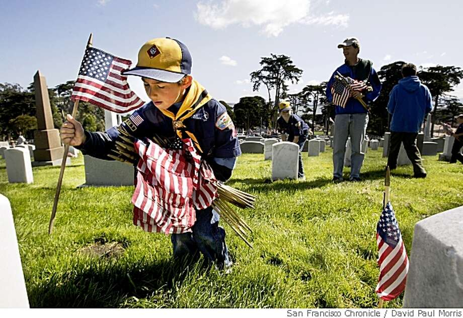 SAN FRANCISCO, CA  - MAY 27: Ethan Frankes 7, from Mill Valley Pack 1 puts flags in front of gravesites at the San Francisco National Cemetary in the Presidio on May 27, 2006 in San Francisco, California. Over 600 scouts from the bay area put down 31,414 flags at the cemetary to honor the fallen.  (Photo by David Paul Morris/The Chronicle) Photo: David Paul Morris, San Francisco Chronicle