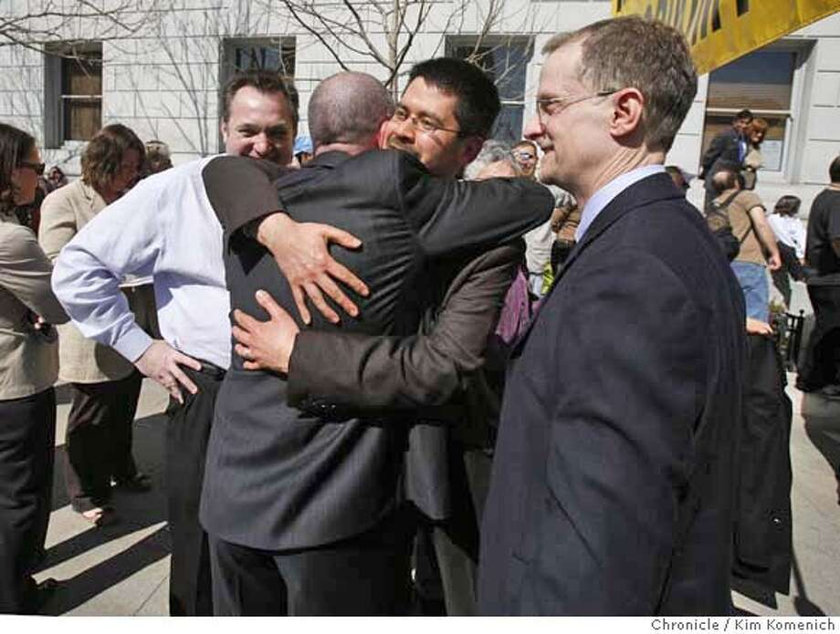 Attorney Shannon Minter, back to camera, is hugged by plaintiff Stuart Gaffney on Tuesday, March 4, 2008 as Gaffney's partner John Lewis, right, looks on. Craig Dziedzic, left, who married the couple on Feb. 12, 2004, also looks on. Minter argued on Lewis and Gaffney's behalf in the same-sex marriage case now before the California Supreme Court at the State of California Building in San Francisco, Calif.  Photo by Kim Komenich / The San Francisco Chronicle Photo: Kim Komenich