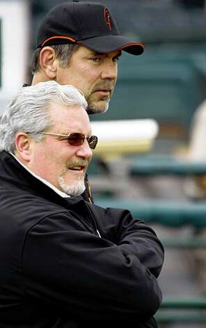 San Francisco Giants general manager Brian Sabean and manager Bruce Bochy, rear, watch pitchers and catchers during their spring training baseball workout in Scottsdale, Ariz., Saturday By Lance Iversen/The San Francisco Chronicle Photo: Lance Iversen, The Chronicle