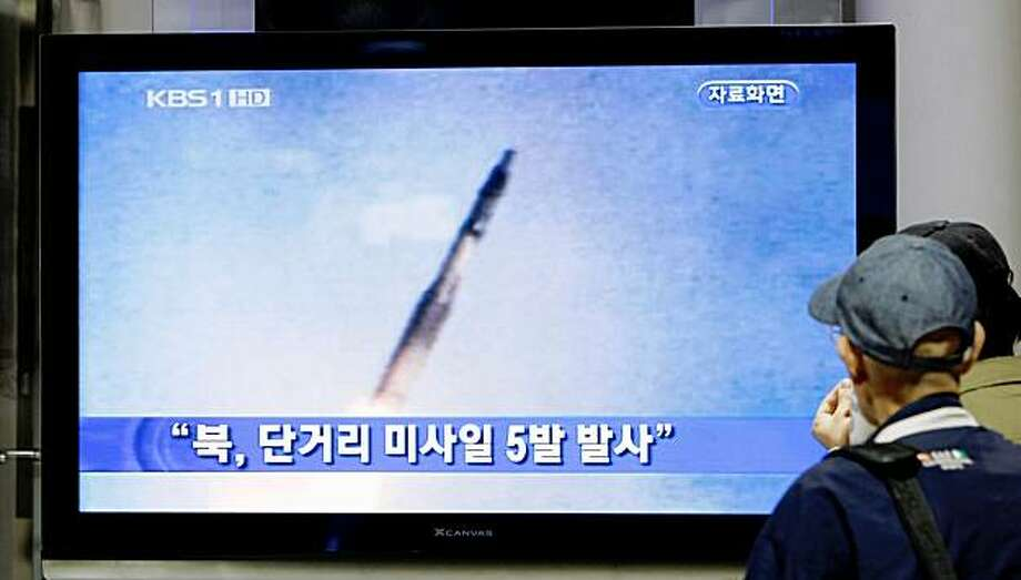 """South Koreans watch TV reporting North Korea's missile test at a Seoul Train Station in Seoul, South Korea, Monday, Oct. 12, 2009. North Korea fired five short-range missiles off its east coast on Monday, a news report said, even as South Korea proposed working-level talks with its communist neighbor. The Korean read """"North Korea fired five short-tange missiles."""" (AP Photo/ Lee Jin-man) Photo: Lee Jin-man, AP"""