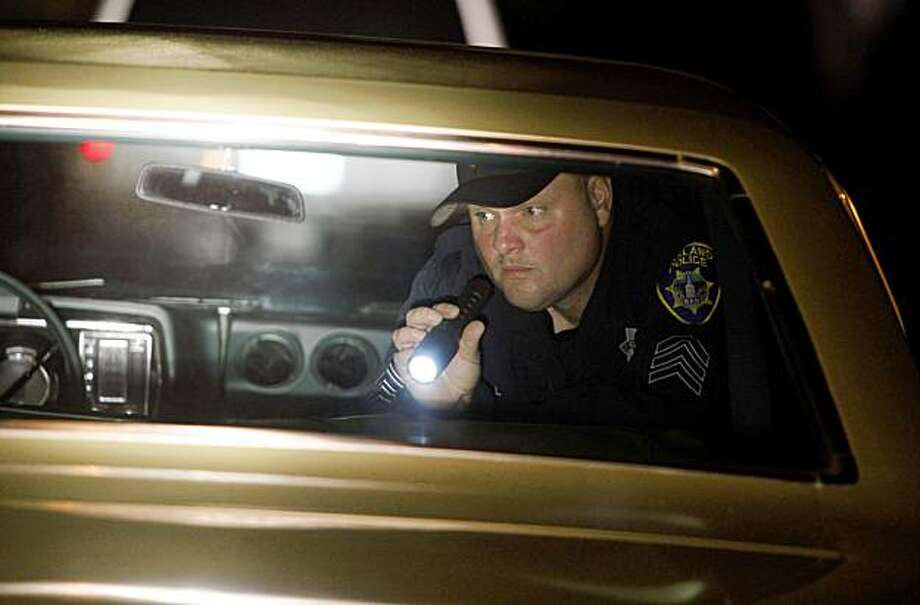 "Sergeant  Dan Royal of the Oakland Police Department search a car for drugs as both he and his partner Chris Moreno take up a active role in stopping ""Sideshows"" activity on the streets of Oakland Calif., October 23, 2009. Photo: Frederic Larson, The Chronicle"
