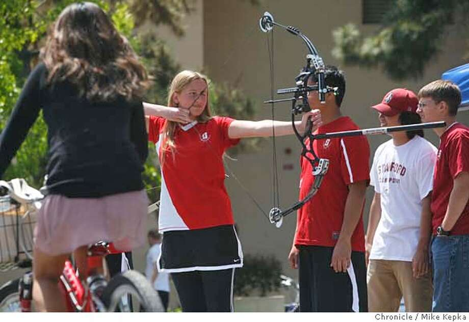 In an effort to recruit new students touring Stanford's campus, Katherine Boren, with the Stanford Archery Club, joins hundreds of other members of various student groups at White Plaza on Thursday April, 24, 2008 in Stanford, Calif. The number of student groups at Stanford and Cal have more than doubled in the last 10 years. will be out in force on White Plaza. Photo by Mike Kepka / San Francisco Chronicle Ran on: 05-19-2008  Katherine Boren of Stanford Archery demonstrates the sport to incoming students at a recruitment event on campus. Photo: Kepka